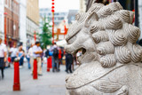 A guardian lion statue located in the crowded London Chinatown - 167763640