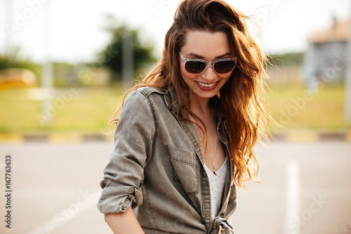Happy smiling woman in sunglasses having fun outdoors
