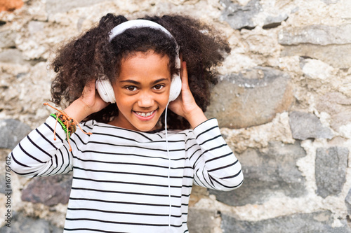 Beautiful african american girl with headphones, listening music