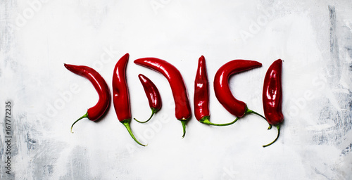 Fresh red hot chili peppers on a gray background, top view
