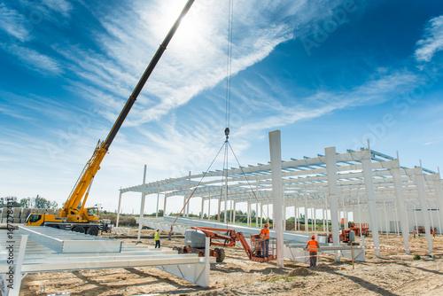 Fototapeta Budowa hali produkcyjnej w fazie montażu konstrukcji stalowej szkieletu za pomocą dźwigu