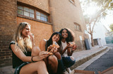 Beautiful girls sitting outdoors by the road eating pizza