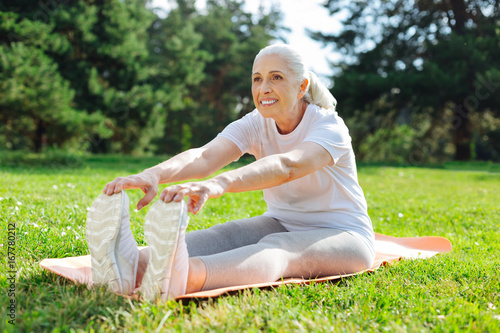 Positive delighted female person touching her sneakers