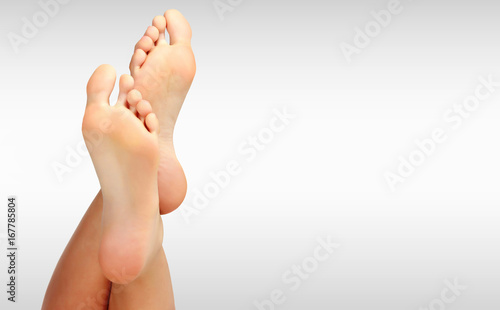 Leinwandbild Motiv Beautiful woman's bare feet against a grey background with copyspace