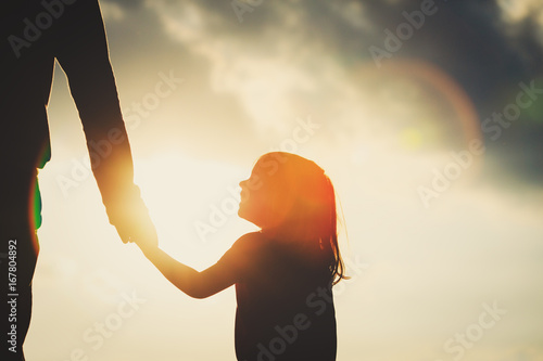 Leinwandbild Motiv silhouette of little girl holding parent hand at sunset