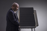Portrait of a black man standing in a voting booth - 167808626