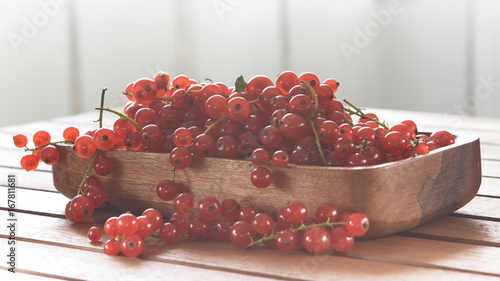 Wall mural Red currant in a wooden cup.