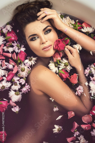 Beautiful woman in the bath with flowers - 167812291
