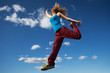 Young woman jumps over blue sky background