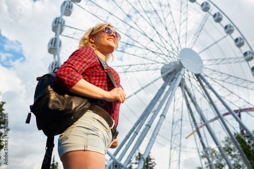 Tuinposter Amusementspark Girl in casualwear on backgrounf of ferris wheel spending time in theme park
