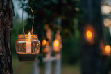 Lamp  with candle  is  hanging  on a tree at night. Wedding night decor. - 167817657