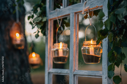 Foto Murales Lamps  with candles  are  hanging  on a tree at night. Wedding night decor.