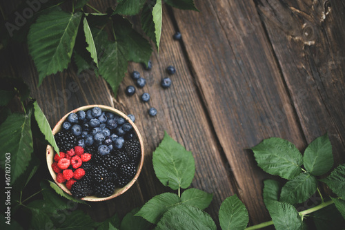 Sticker Bowl of freshly picked berries over wooden table and greenery