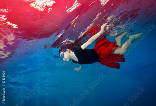 Happy little girl swimming and playing underwater on a blue background in a red skirt Poster