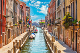 Street in Venice with canal boat and blue sky white cloud