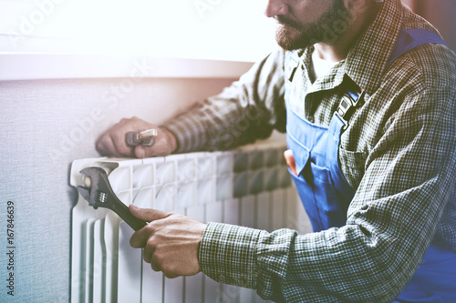 Foto Murales service man with wrench near radiator