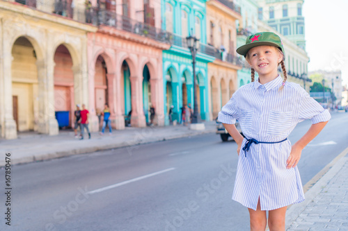 Adorable little girl in popular area in Old Havana, Cuba. Portrait of kid background vintage classic american car
