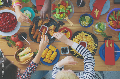 Top view of group of people having dinner together while sitting at wooden table. Food on the table. People eat fast food. - 167855065