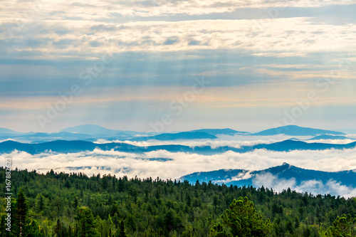 Breathtaking sunrise and mist over the tops of mountains and woods