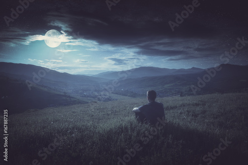 Human sitting on a hill in and enjoy moon rising. Instagram stylization