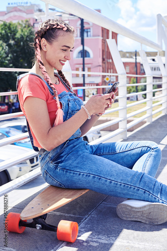Foto op Aluminium Skateboard Pretty girl surfing in phone sitting on skateboard