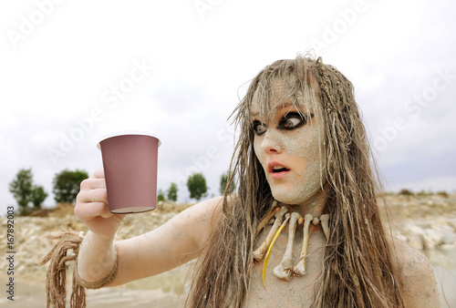 A girl gets herself made up as a prehistoric  cave woman and is covered with mud Poster