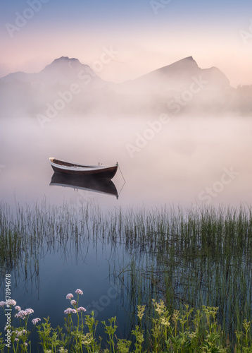 Fototapeta Very peaceful summer night with wooden boat and fog in Lofoten, Norway