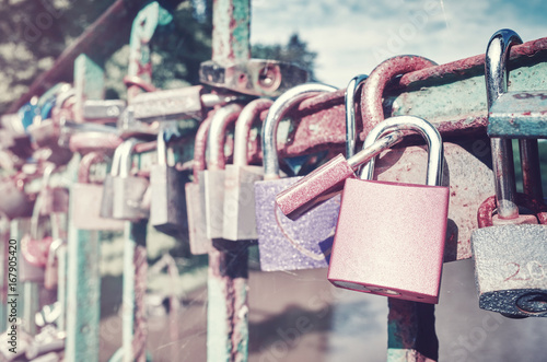 Vintage toned picture of old rusty padlocks on a bridge, love symbol, shallow depth of field.
