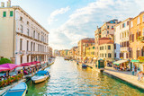 Bright Venice street with canal and boats and typical Venetian buildings.