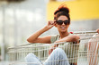 Girl in sunglasses sitting inside a shopping trolley outdoors