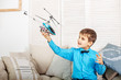 Quadro The little boy is played on an airplane. The concept of lifestyle, childhood and family.