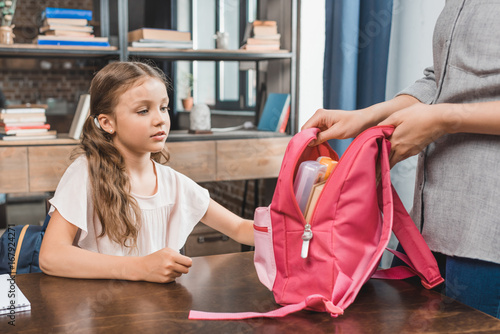 mother and pensive little daughter preparing backpack for school