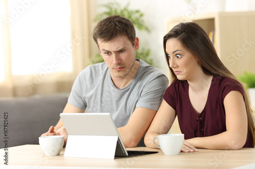 Confused couple receiving on line news - 167925625