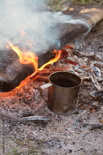 metal mug with tea around the campfire in the campaign