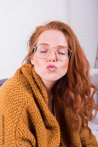 Juliste Portrait schöne rothaarige Frau in oranger Strickjacke mit Kussmund
