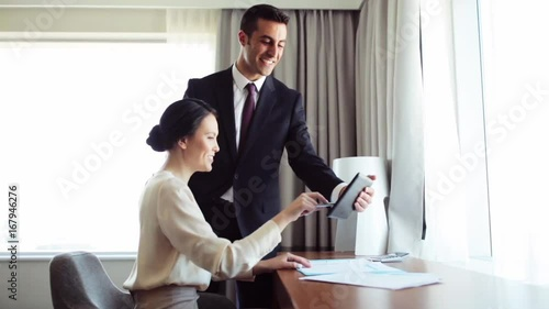 business team with papers and tablet pc at hotel