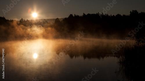 Rising sun in the fog above a lake