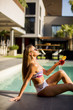 Quadro Young woman by the swimming pool with coctail