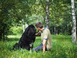 The owner communicates with his dog. A large black Newfoundland. Forest, trees, birch, grass, summer