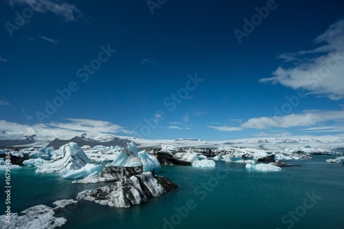 Iceland - Glacier behind giant icebergs on glacial lake, aerial photograph