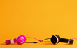 Quadro Pink and black headphones entwining their wires together on a yellow background