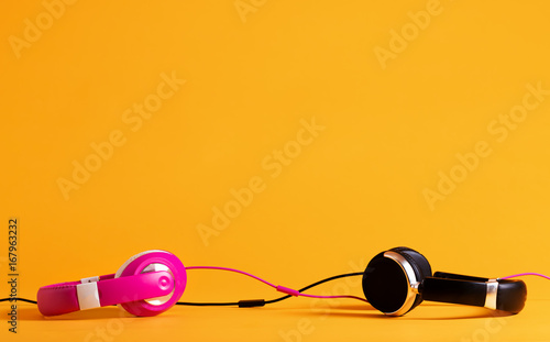 Pink and black headphones entwining their wires together on a yellow background