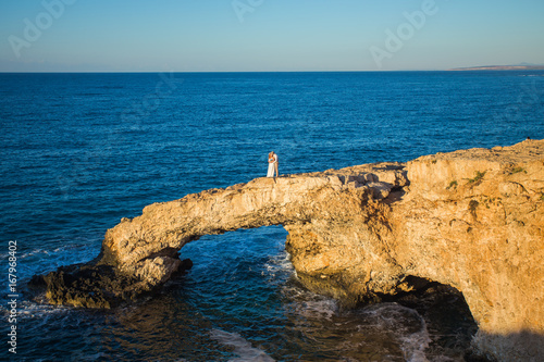 Foto op Plexiglas Cyprus beautiful gorgeous blonde bride and stylish groom kissing on rocks, on the background of a sea, wedding ceremony on cyprus.