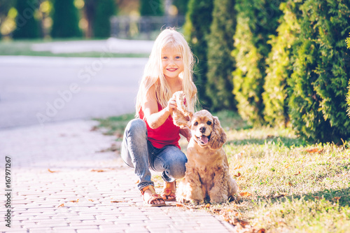 Little beautiful girl is walking with a dog in the park