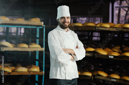 young handsome man baker in white uniform and cap on background bakery