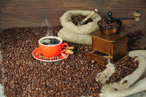 Fotobehang Koffiebonen Coffee, cappuccino or espresso smoke and cinnamon sticks on a wooden table with a coffee grinder, red cup