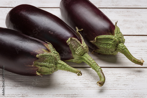Three fresh eggplants on a white wooden surface.