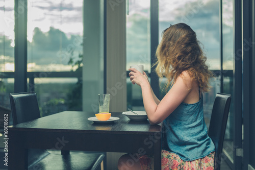 Young woman having breakfast by the window in the city Poster