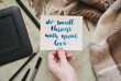 """Flat lay of artist home office in bed. Female hand holding card with handwritten inspirational quote """"do small things with great love"""""""