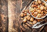 Nuts with Nutcracker in a bowl on the old Board. - 168022017